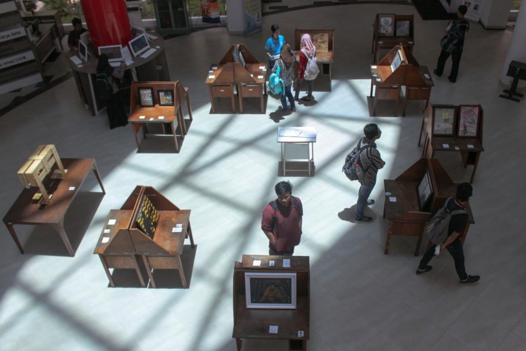 """Pengunjung menyaksikan sejumlah karya lukis dan instalasi di Perpustakaan Pusat UGM Yogyakarta, Rabu (25/2). Deretan karya tersebut merupakan bagian dari pameran yang diselenggarakan Unit Seni Rupa (User) UGM bertemakan """"Masih Ada Yang Ingat"""". Pameran tersebut merupakan bagian dari  peringatan Hari Pers Nasional sekaligus Dies Natalis Perpustakaan UGM. ©Nurrokhman.bal"""